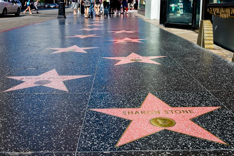 """Neben dem allgemein betörenden Flair der Stadt gibt es eine Vielzahl an Attraktionen aufzusuchen. Am Walk of Fame entlang des Hollywood-Boulevards sind über 2.000 Filmstars von der Stummfilm-Zeit bis heute verewigt. Hebt man den Kopf von den zahlreichen Sternen, blickt man mit Sicherheit direkt in ein Souvenir-Geschäft, das jeden erdenkbaren Kitsch zum Thema Film verkauft. Sogar originale Autogramme und Drehbuchmanuskripte können erstanden werden. Im Hollywood Entertainment Museum kann man die Kommandobrücke von """"Star Trek"""" betreten oder in der Bar von """"Cheers Platz"""" nehmen. Darüber hinaus sind eine Menge an Requisiten und Kostümen aus Filmen aller Generationen ausgestellt und man erfährt einiges über die Entstehung eines echten Hollywood-Films. Ähnliches an Kostümen, Requisiten und Make-up, aber viel nostalgischer, erlebt man im Hollywood History Museum, das sich auf die gute alte Zeit des glamourösen Hollywood spezialisiert hat, als Buster Keaton und Charlie Chaplin Filmgeschichte schrieben. Das Hollywood Heritage Musuem widmet sich ganz der Entstehung des ersten Spielfilms, der 1913 von Cecile B. DeMille gedreht wurde und zeigt Bilder von dem damals noch kleinen Farmerdorf."""